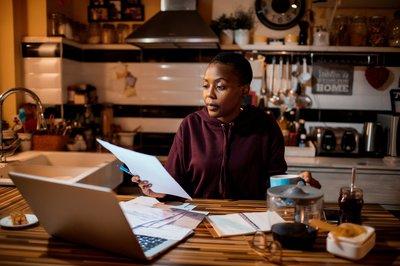 Woman paying bills at kitchen table