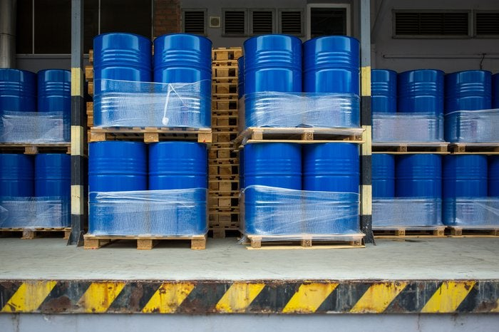 Large blue metal barrels stacked together at a loading dock.