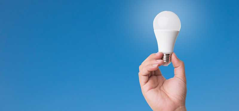 Man holding an LED lightbulb.
