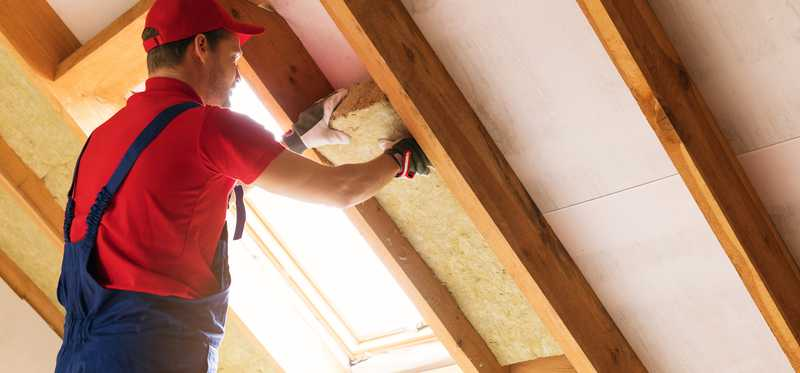 Man installing insulation in an attic.