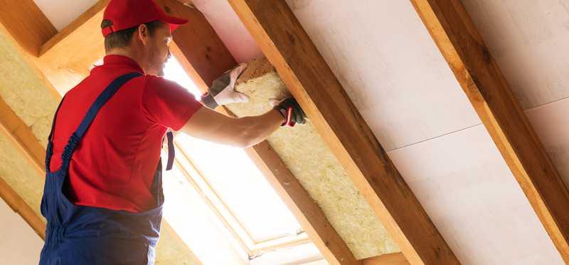 Man installing insulation in an attic.