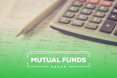 The words mutual funds over financial data and a pen and calculator.
