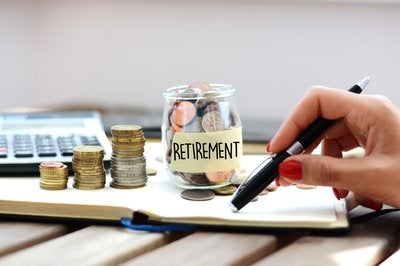 Hand holds pen near jar of coins labeled Retirement.