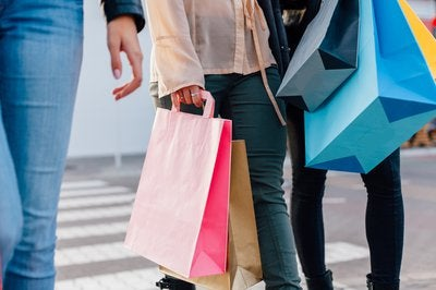 Three people holding shopping bags.