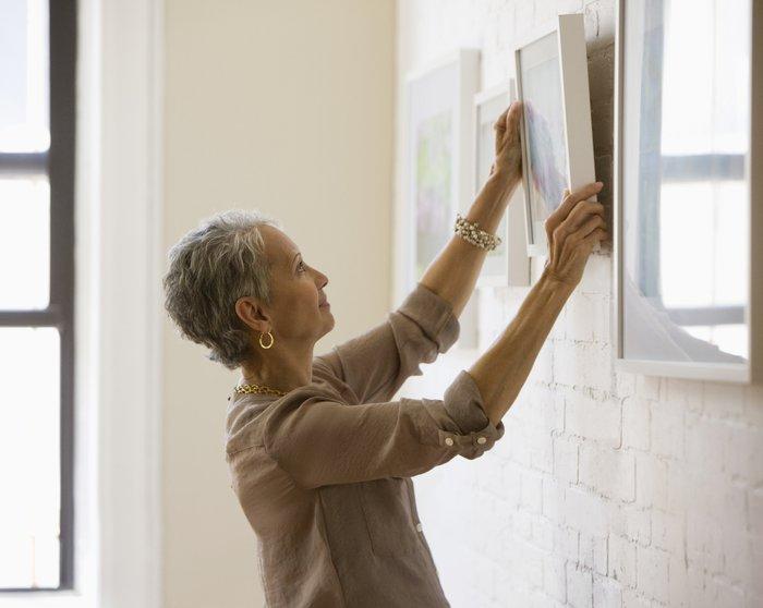 Senior Woman Hanging Frame On Wall