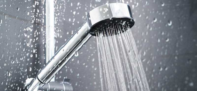 A showerhead with water flowing.