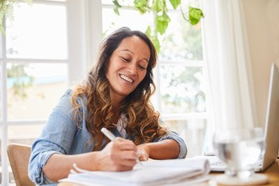 Woman writing in notebook in sunny living room