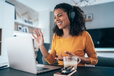 Woman wearing headphones while sitting at kitchen table and waving to coworkers on videoconference