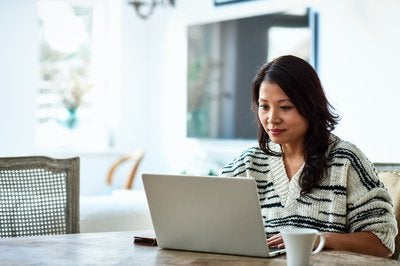 Woman wearing sweater and using her laptop