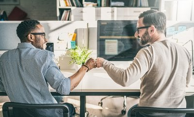 Coworkers sitting at their desk fist-bumping each other