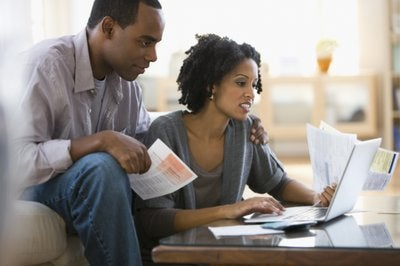 Couple looking over finances on laptop