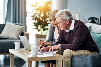 Senior couple looking at laptop and documents