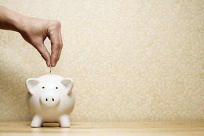 Person putting coin into a piggy bank.