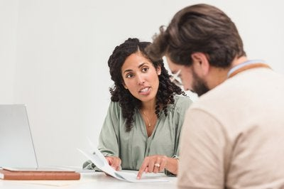 Businessman and businesswoman sitting at table reviewing documents
