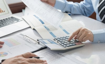 Person using calculator while looking over accounting spreadsheets