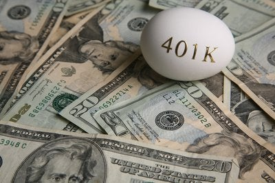 An egg with 401(k) written on it on top of a pile of cash
