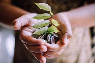 Hands holding coins with green plant sprouting out of them.