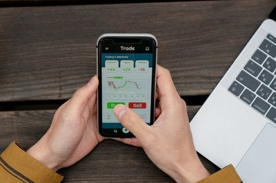 Person using mobile trading app to buy and sell stocks.