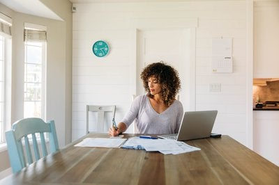 Woman sitting at kitchen table with laptop open and paying bills