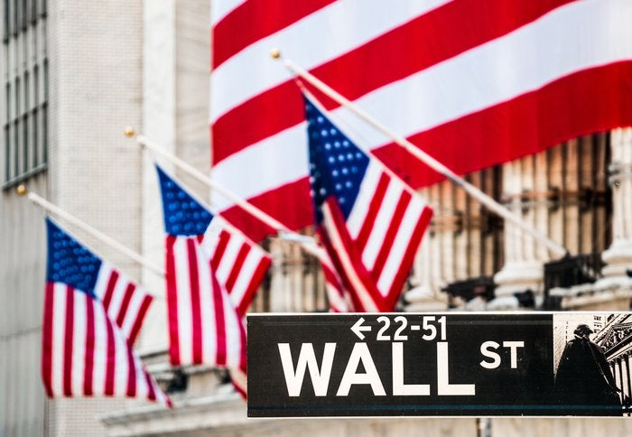 The facade of the New York Stock Exchange draped in a large American flag, and the Wall St. street sign in the foreground.