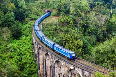 Blue train on bridge.