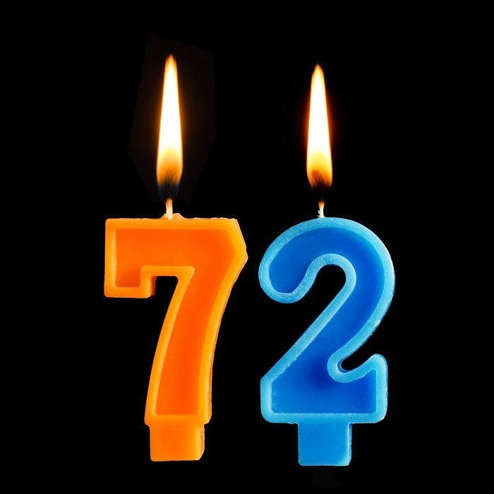 Two lit birthday candles reading 72 against black background