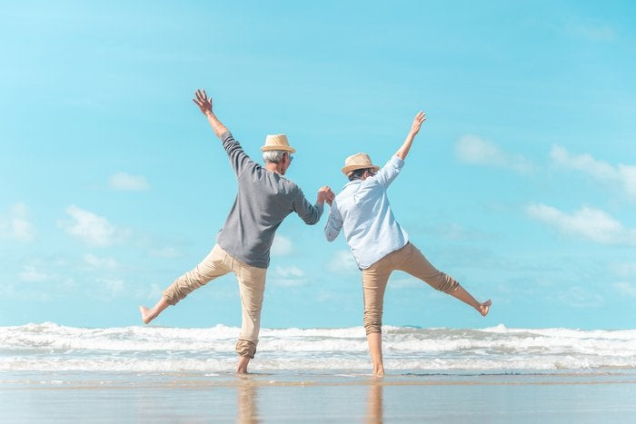 Two older men on beach holding hands with arms in the air