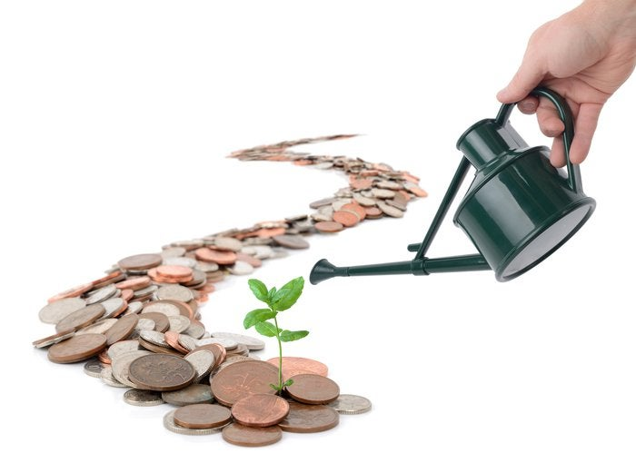 Watering can nourishing a trail of coins