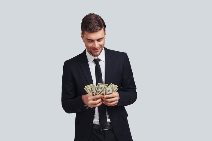 Wealthy man in suit counting his money