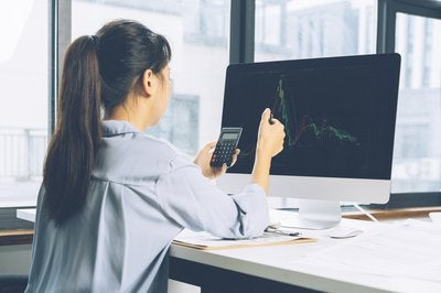 Women using calculator while looking at stock chart on computer screen