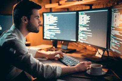 Young man in front of three computer monitors.