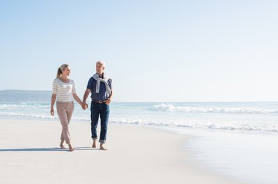 An older couple walks on a beach
