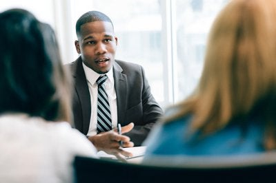 business person giving advice to two clients