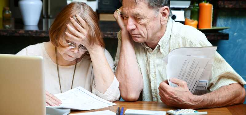 An elderly couple looking through paperwork together.
