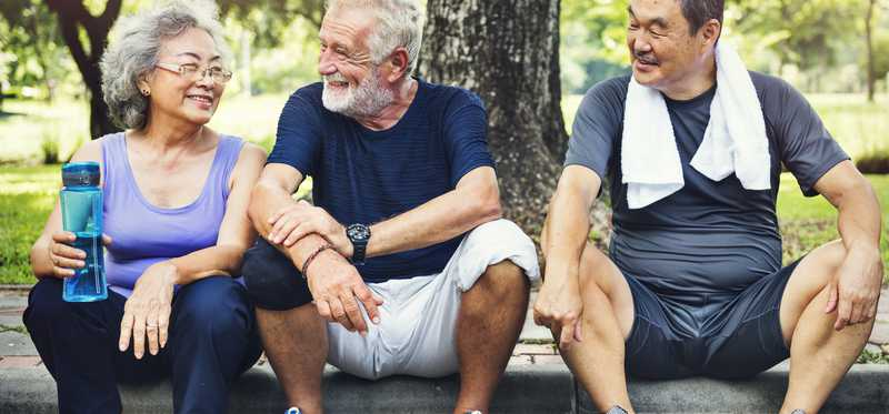 Three older people sitting on the curb of a road after a workout.