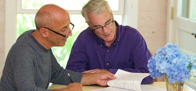 Two older men looking through paperwork together.