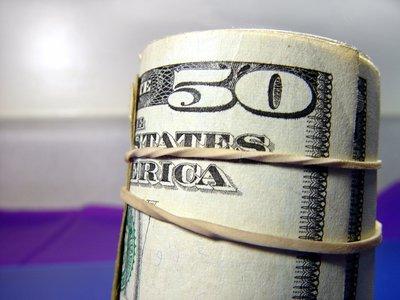Fifty dollar bill on outside of money roll.