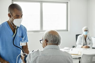Doctor in scrubs taking heart rate of patient