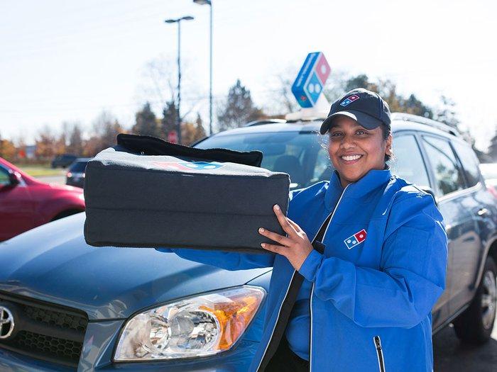 A Domino's driver delivering pizza