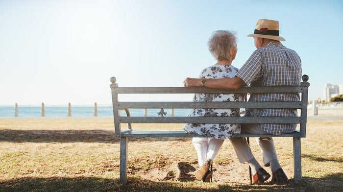 Elderly senior couple sitting on a bench on the beach