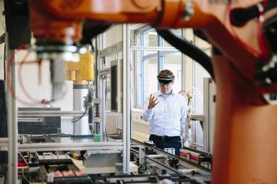 Engineer with a HoloLens placing virtual robotic arm into the production line.jpg