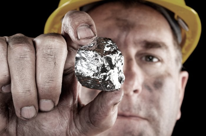 Man in hard hat holding chunk of raw silver towards the camera