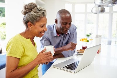 Mature man and woman sitting in kitchen looking at laptop computer and smiling.