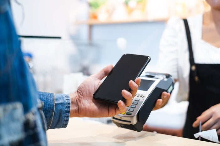 A person holds their smartphone near a payment processing device.