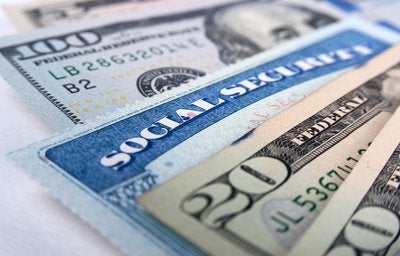 A Social Security card mixed in with a fan of paper bills