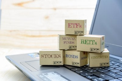 Boxes sitting on laptop keyboard all labeled with types of financial instruments like ETFs, REITs, stocks, etc.