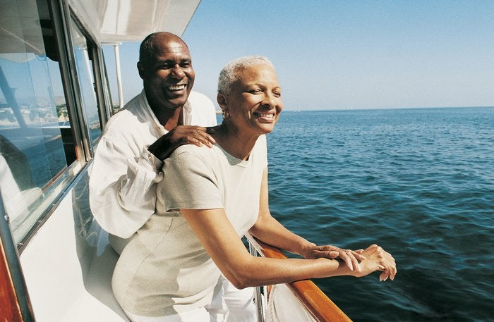 Two people smiling while standing on the side of a boat.