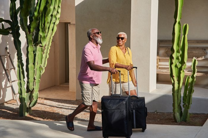 senior couple rolling suitcases down the street and smiling