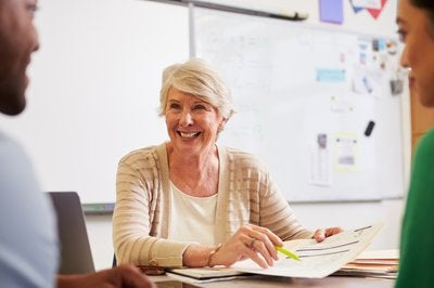 Senior woman in classroom talking to to younger adults and smiling