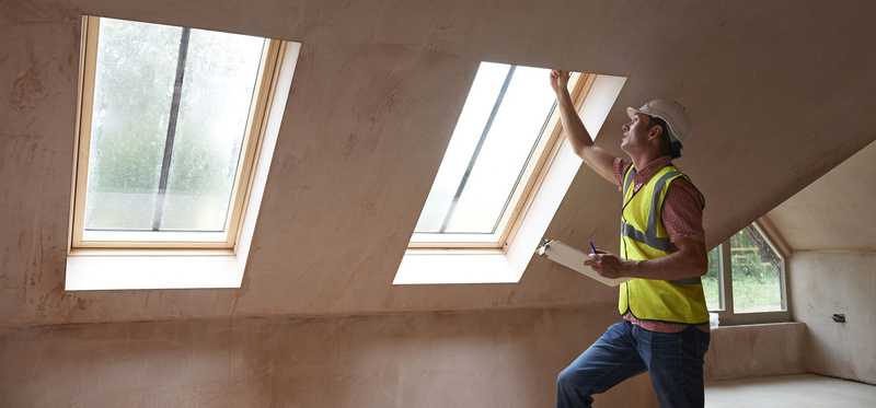 A man measures skylights in a ceiling.